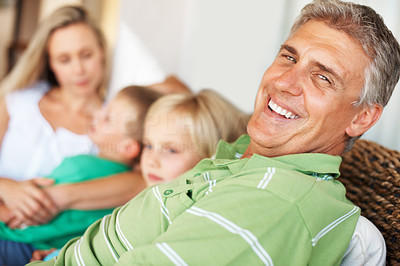 Buy stock photo Portrait of mature man smiling at home with his family in the background