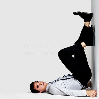 Buy stock photo Portrait of a crazy young man posing in upside down posture against grey background