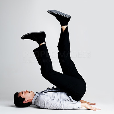 Buy stock photo Portrait of a crazy young business man posing in upside down posture against grey background