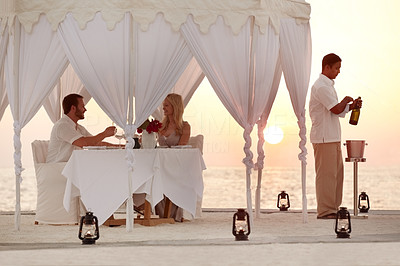 Buy stock photo Portrait of a couple having a  romantic dinner at the beach under a decorative canopy at sunset