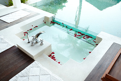Buy stock photo A beautiful modern jacuzzi bath with rose petals floating in it next to a swimming pool