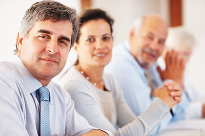 Buy stock photo Portrait of confident business man with colleagues in the background