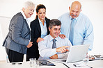 Business people looking at laptop at meeting table in office