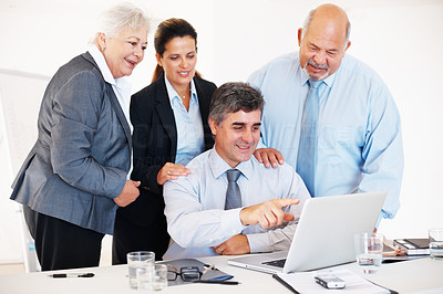 Buy stock photo Mature business man pointing at the laptop monitor with executives near by