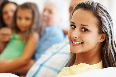 Buy stock photo Closeup portrait of pretty teen girl with family sitting in the background
