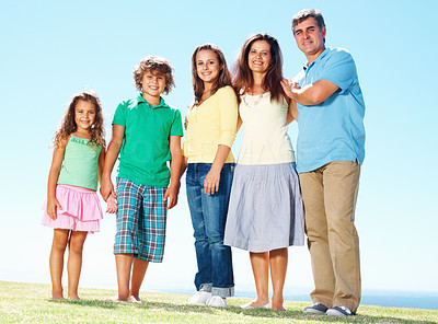 Buy stock photo Family portrait - Family standing together on grass against sky