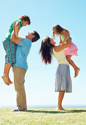 Buy stock photo Side view of mature parents carrying children on grass during weekend