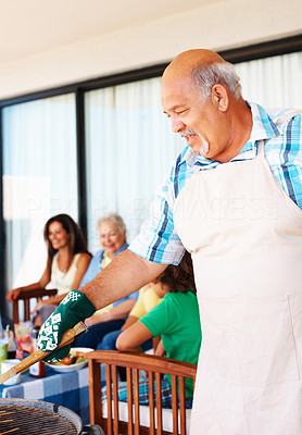 Buy stock photo Portrait of an old man barbecuing with family in the background at the weekend