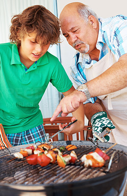 Buy stock photo Closeup of grand father teaching grand son to barbeque steaks