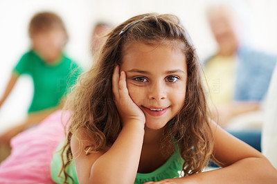 Buy stock photo Closeup portrait of cute girl relaxing with family sitting in the background