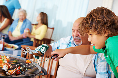 Buy stock photo Senior man and grandson barbecuing food with family in the background
