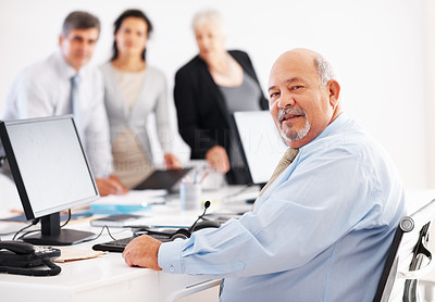 Buy stock photo Senior business man at his desk with colleagues in background