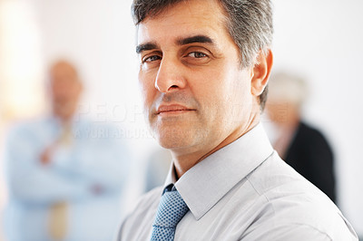 Buy stock photo Closeup of serious business man with colleagues in background