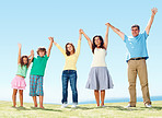 Family raising hands outdoors against clear blue sky