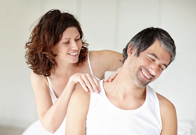 Mature woman giving a shoulder massage to her happy husband