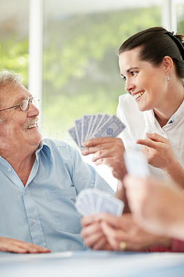Beautiful woman helping an elderly man in playing game of card