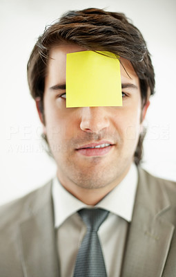 Business man with a blank adhesive note on the forehead