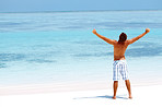 Nature inspiration - Energetic young man raising hands on the beach