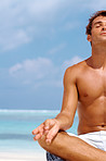 Relaxed young man doing yoga on the beach