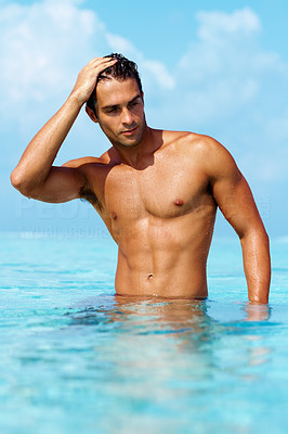 Buy stock photo Torso of a gorgeous guy standing in waist deep water looking away thoughtfully with brilliant blue water and sky - copyspace