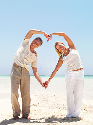 Middle aged couple making love sign at the beach
