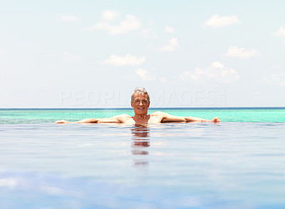 Mature guy in water pool by the sea