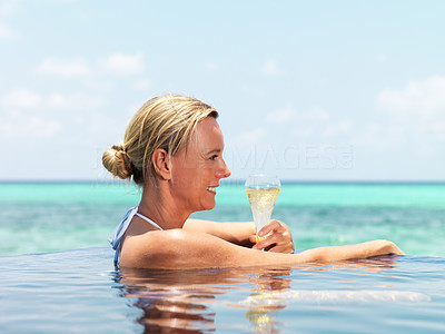 Pretty woman in the water pool with cocktail