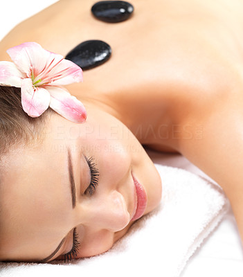 Buy stock photo Smiling female face - Hot stone massage in the day spa - Portrait of a beautiful young woman at the day spa with black stones on her bare back