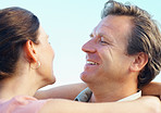 Smiling mature couple looking at each other with arms around