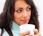 Closeup of a beautiful young lady holding coffee cup and looking away