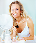 Happy young woman looking at the mirror, applying make up