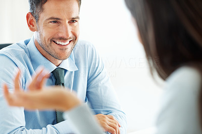 Attractive male executive in conversation with colleague