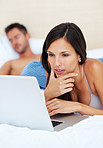 Beautiful woman using laptop in bed