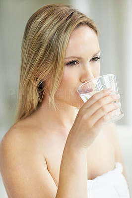 Young woman wrapped in a towel and drinking a glass of water