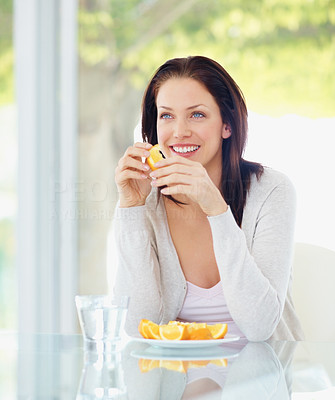 Cute young woman eating sliced oranges