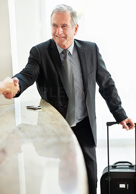 Happy senior business man shaking hand at the hotel reception