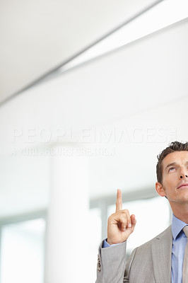Cropped image of a young business man pointing up - copyspace
