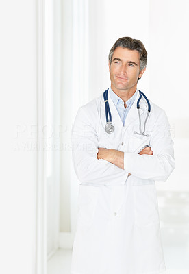 Contemplative male doctor looking at copyspace in corridor