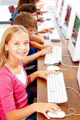 Small girl using computer with children in background
