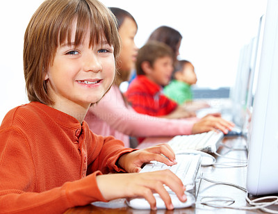 Small boy using computer with children in background