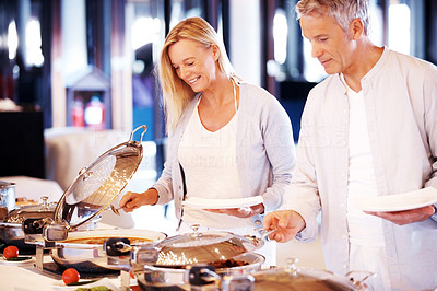 Happy mature couple serving food at buffet