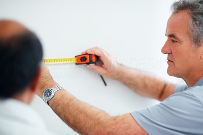 Handyman taking wall measurements along with a colleague