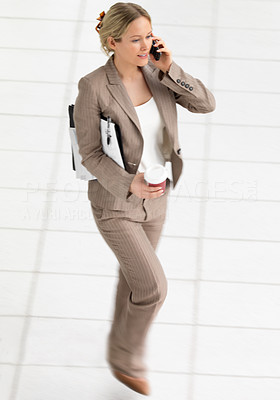 Young beautiful business woman walking and using her cell phone