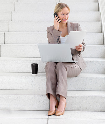 Young beautiful business woman sitting on steps, using cell phone, working on her computer