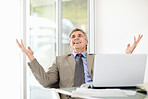 Happy mature businessman with stretch hands and laptop on desk