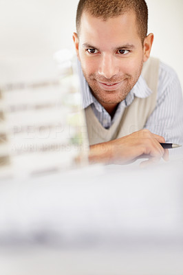 Smiling architect holding pen while looking at building model