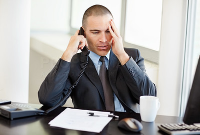 Tensed middle aged business man talking on telephone in office