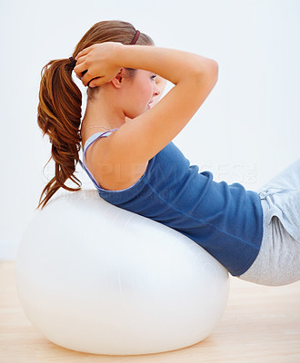 Sexy young female exercising on a fitness ball