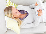 Young businesswoman lying on sofa and writing documents