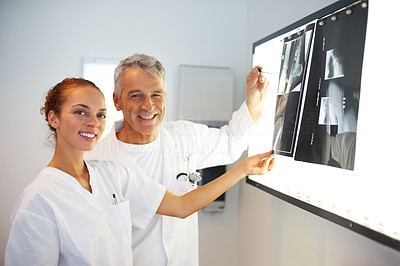 Smiling doctors examining an x-ray over light